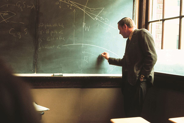Neil Armstrong writes on a chalkboard in the UC College